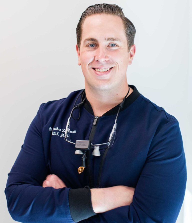 dr jonathan lopresti smiling with arms crossed