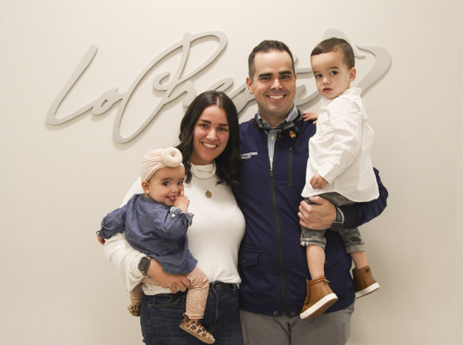 dr matthew lopresti with wife and two kids smiling in office
