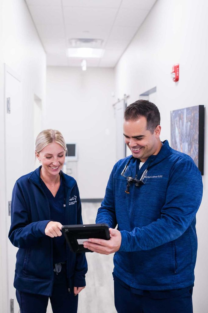 dr showing team member ipad in hallway of office